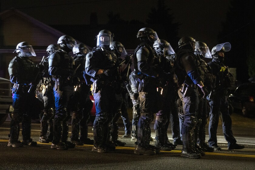 Portland, Ore., police officers stand together on a street.