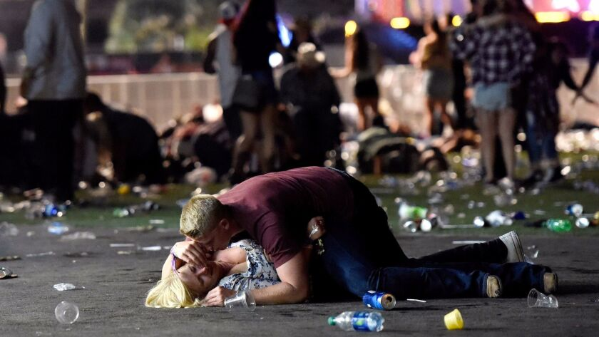 A man lays on top of a woman as others flee the Route 91 Harvest country music festival grounds. Eyewitnesses describe the harrowing scene that left more than 20 people dead and more than 100 others injured.