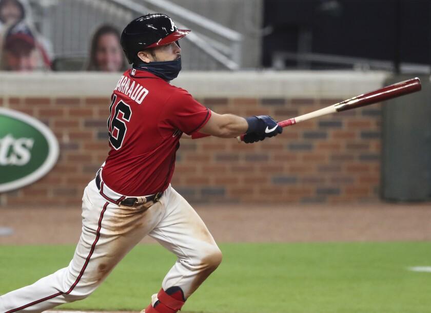 Travis D'Arnaud, de los Bravos de Atlanta, batea un doble productor frente a los Mets de Nueva York, el viernes 31 de julio de 2020 (Curtis Compton/Atlanta Journal-Constitution via AP)