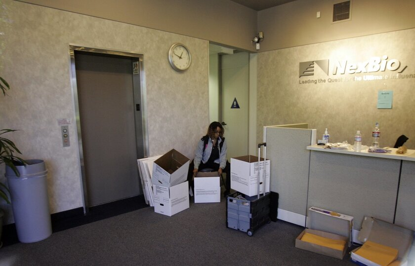 An unidentified woman handled boxes inside the lobby of NexBio after more than 20 federal agents took over the San Diego company's office as part of a white-collar crime investigation.