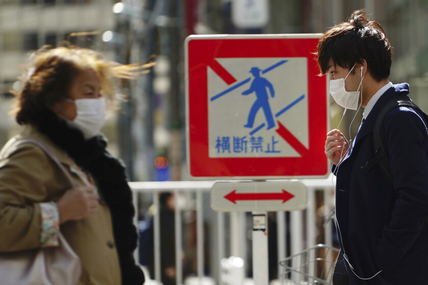 Pedestrians with protective masks on a street Thursday, March 5, 2020, in Tokyo. The number of infections of the COVID-19 disease spread around the globe. (AP Photo/Eugene Hoshiko)