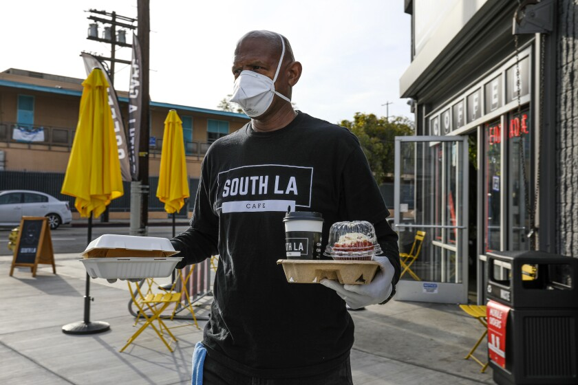 Joe Ward-Wallace delivers a takeout order at South LA Cafe on March 28.