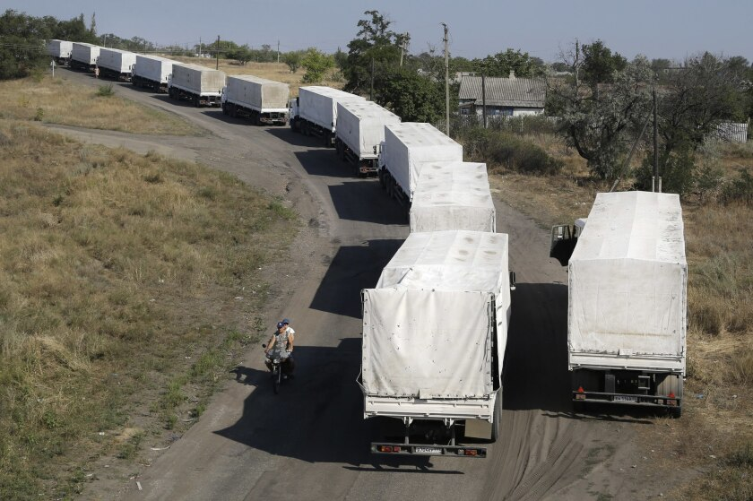 Trucks from a controversial Russian aid convoy to Ukraine stand in line as they wait to return to Russia at a border post near Izvaryne in eastern Ukraine on Aug. 23.
