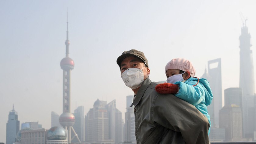 A man and his child wear protective face masks in Shanghai, China, in 2013.