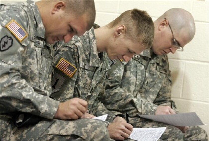 Staff Sergeants, Clifton Crowder, front, Justin Ellis, center, and David Gavula, back, fill out their medical paperwork, prior to receiving the H1N1 vaccine, in the Solomon Center, at the Army's Ft. Jackson Training Center, in Columbia, S.C., Wednesday, Dec. 9, 2009. (AP Photo/Brett Flashnick)