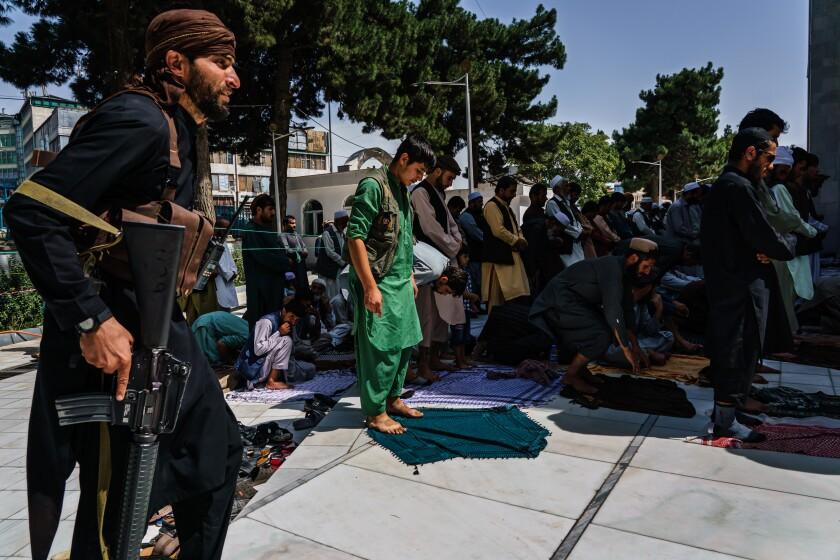 Taliban fighters set down prayer mats during Friday prayers
