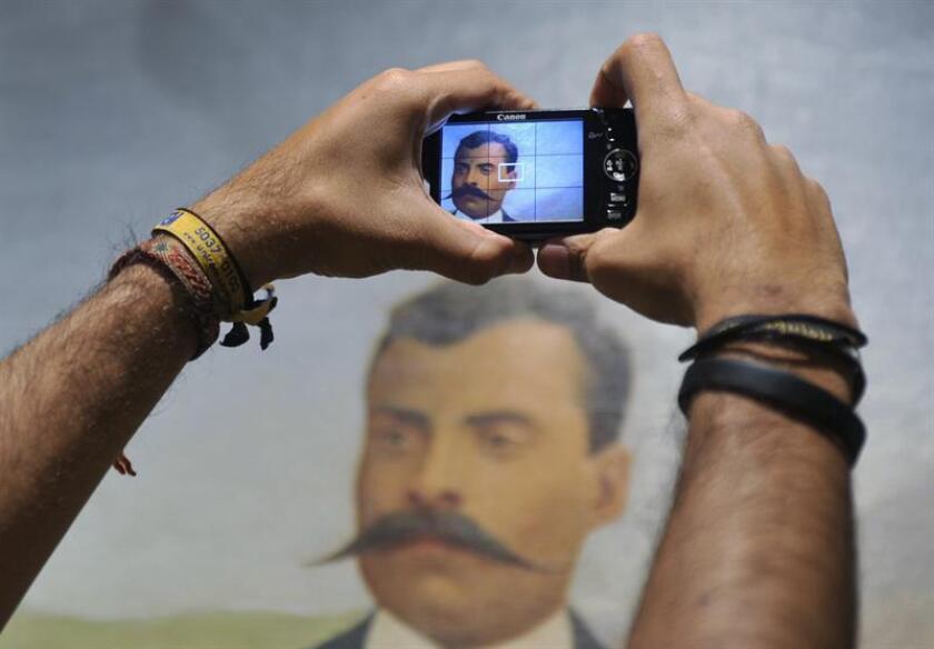 """Un hombre toma una fotografía de un óleo sobre tela del revolucionario mexicano Emiliano Zapata (1879-1919), el martes 10 de abril de 2012, durante la muestra """"El Zapatismo: La voz de los pueblos"""". EFE/Archivo"""