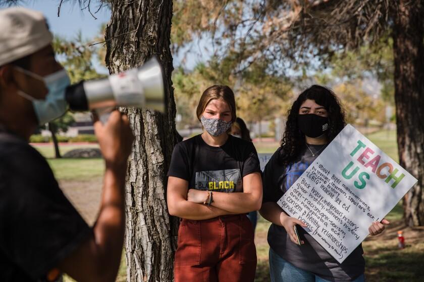 Brenna Seaboch, izquierda, y Lana Alany escuchan a un orador en una protesta