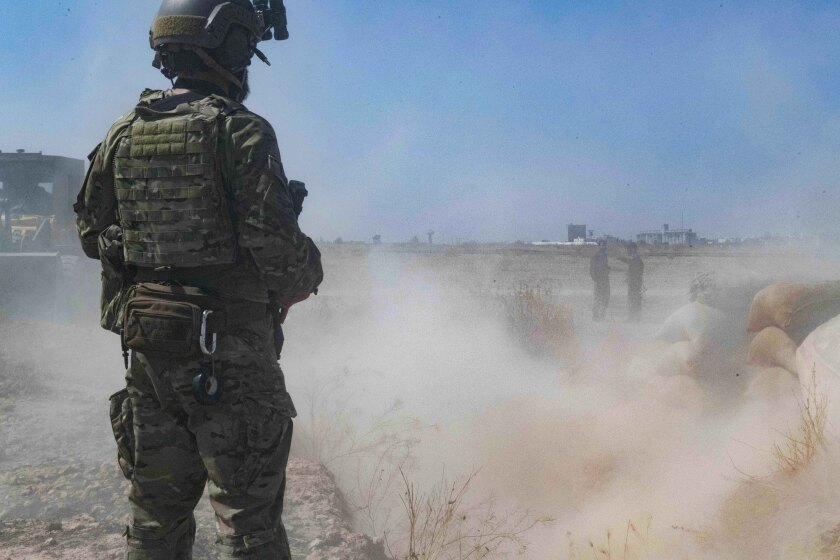 "In this Sept. 21, 2019, photo, released by the U.S. Army, a U.S. soldier oversees members of the Syrian Democratic Forces as they demolish a Kurdish fighters' fortification as part of the so-called ""safe zone"" near the Turkish border. (U.S. Army photo by Staff Sgt. Andrew Goedl via AP)"