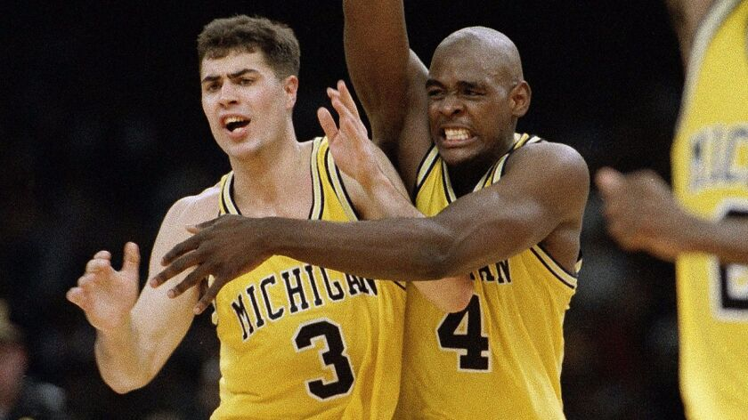 Michigan's Chris Webber (4) and Rob Pelinka (3) celebrate after beating Kentucky, 81-78, in overtime to advance to the 1993 NCAA Tournament final on April 3, 1993.