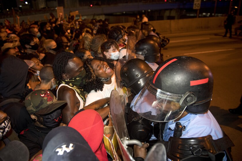 New Orleans police clash with protesters after a largely peaceful protest march, on top of the bridge on Wednesday, June 3, 2020, days following the death of George Floyd in Minnesota. Floyd died after being restrained by Minneapolis police officers on May 25. (Chris Granger/The Advocate via AP)