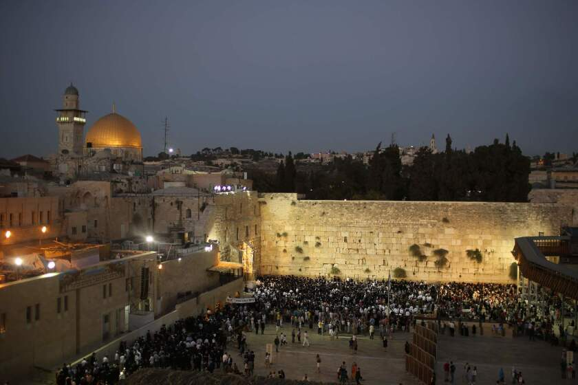 Jewish worshipers welcome the Sabbath by praying at the Western Wall in Jerusalem's Old City on Friday. At the upper left are the Al Aqsa mosque and Noble Sanctuary.
