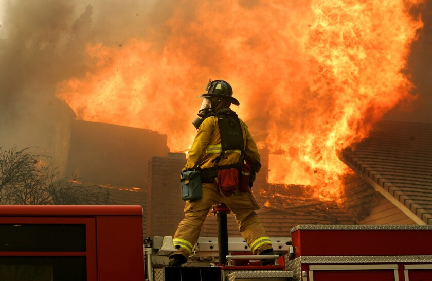 A San Diego firefighter battles a fire at a house in Rancho Bernardo on Oct. 22, 2007. Gov. Gavin Newsom's wildfire strike force released a report Friday with recommendations for reducing the risk of deadly blazes in the state.