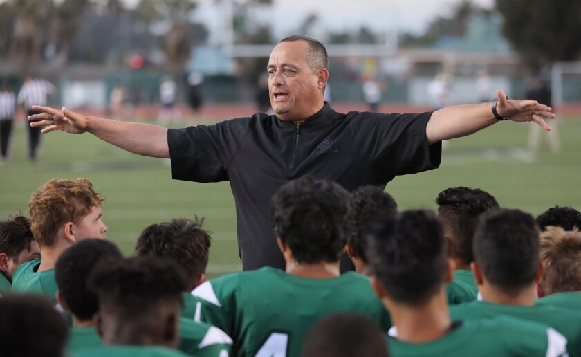 Oceanside head coach David Rodriguez meets with his team before the game.