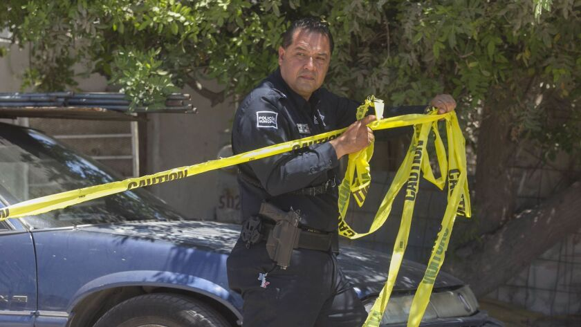 TIJUANA, BAJA CA.- Aug.1-7, 2017, A Tijuana municipal police officer put up yellow tape at the scene where a woman was gunned down while eating lunch at an outdoor market, two days after another murder just one block away. During the first week of August, 2017, there were 48 people murdered in Tijuana. PHOTO/JOHN GIBBINS, Staff photographer, San Diego Union-Tribune) copyright 2017