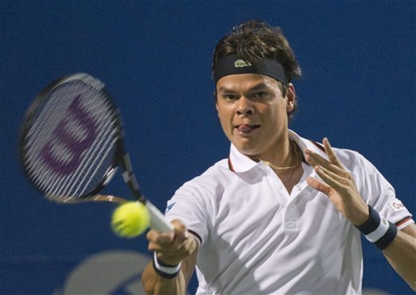Milos Raonic of Canada returns the ball against John Isner of the United States during Rogers Cup quarterfinal tennis action in Toronto on Friday, Aug. 10, 2012. (AP Photo/The Canadian Press, /Nathan Denette)