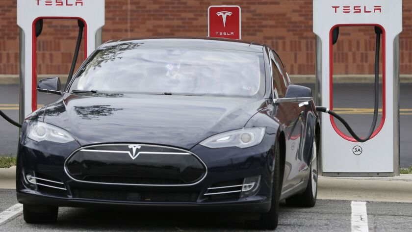 FILE - In this Saturday, June 24, 2017, file photo, a Tesla car recharges at a charging station at C