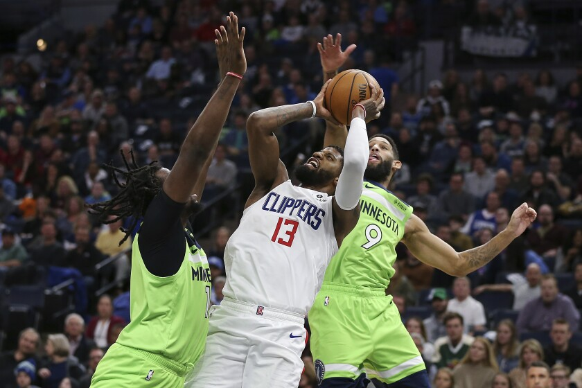 Clippers forward Paul George tries to score despite the double-team defense of Minnesota's Naz Reid, left, and Allen Crabbe (9) during a game Feb. 8, 2020, in Minneapolis.