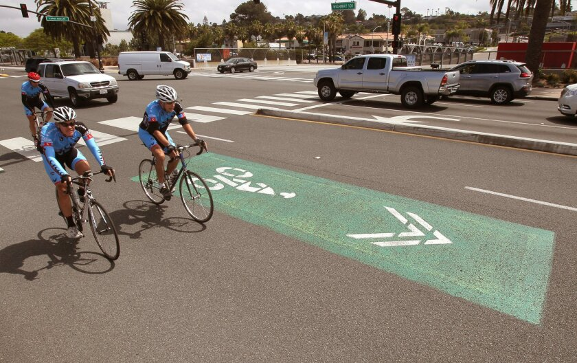 "Cyclists speed past one of the ""sharrow"" markings painted on the pavement on this section of Highway 101 near Lomas Santa Fe Drive."