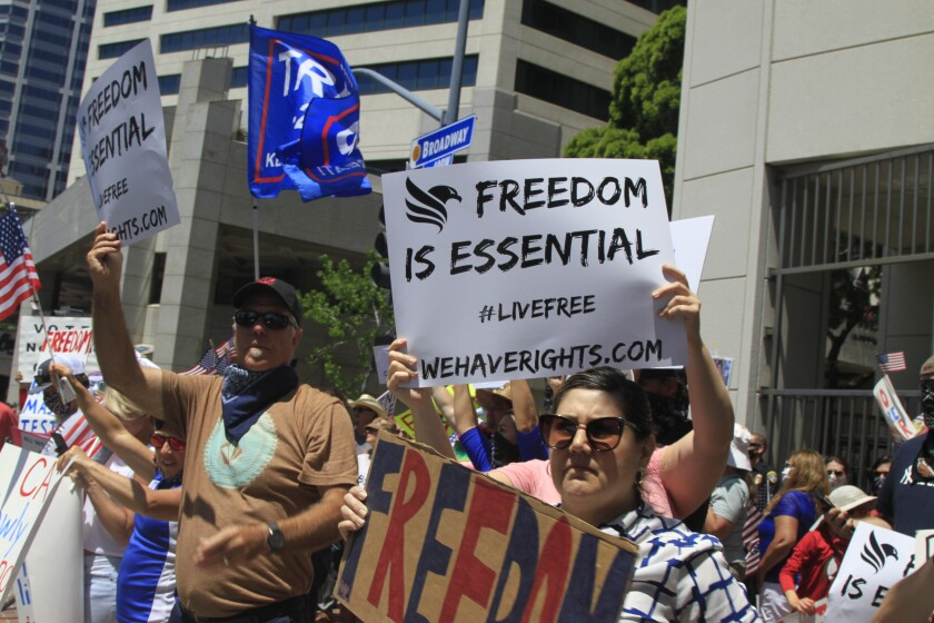 Anti-lockdown protesters rally in downtown San Diego on May 1, 2020, calling on state and local officials to fully reopen the economy. Many in attendance waved branded signs provided by a new group called We Have Rights.