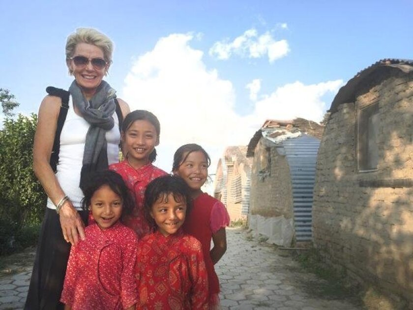 Kathleen Rafaat in the village of Harsidi with some of its youngest residents. Rafaat helped build 20 shelters in Nepal and is now working toward funding a school science lab and library.