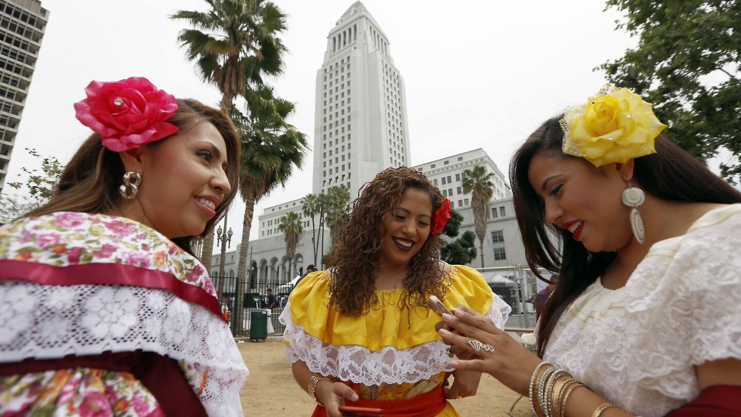 Janet Arteaga, from left, Gaby Arteaga, middle, and Luli Arteaga, known as the musical group Las Hermanas Arteaga, wait to go on stage at the 27th Fiesta Broadway in Los Angeles on Sunday.