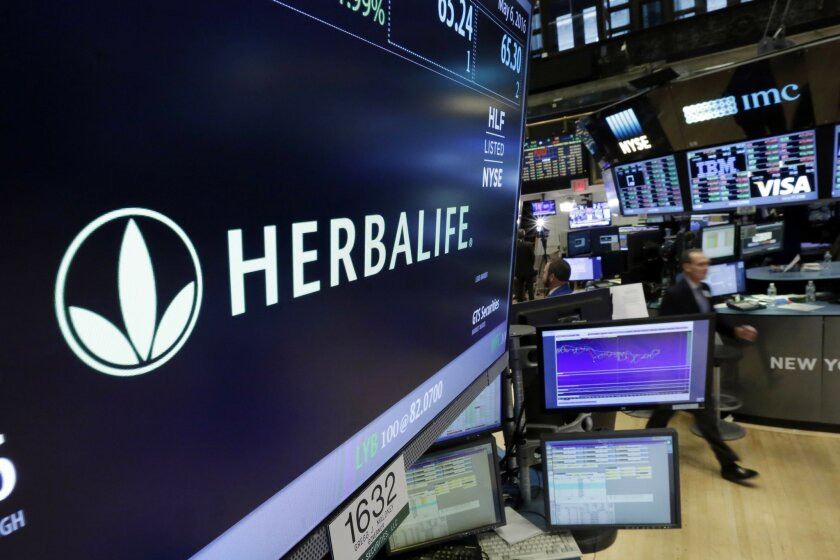 FILE - In this May 6, 2016 file photo, the Herbalife logo appears above the post where it trades on the floor of the New York Stock Exchange.   The Federal Trade Commission is closing an investigation of Herbalife and the multinational, nutritional supplements company will to pay $200 million to se