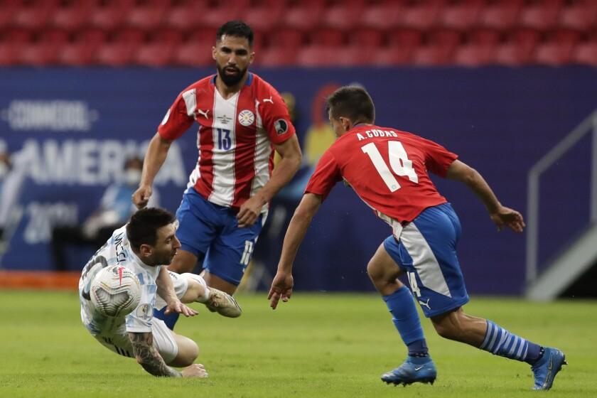 El delantero argentino Lionel Messi (izquierda) cae al piso en el partido contra Paraguay en la Copa América