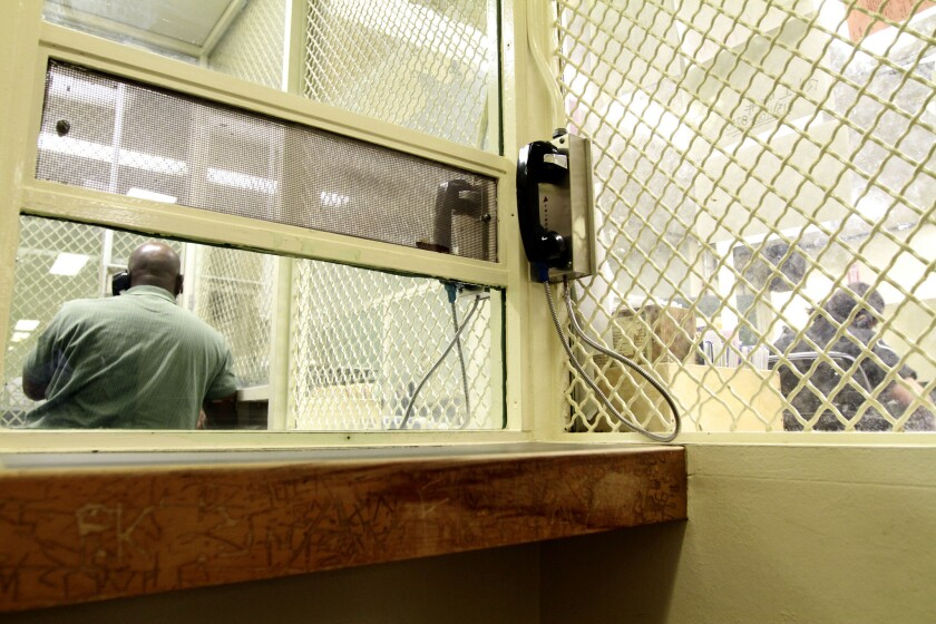 A visitor talks to a felony floor prisoner in the visiting area of LAPD's Metropolitan Jail.