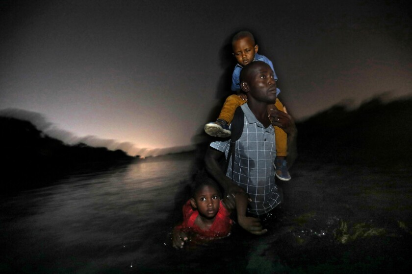 RIO GRANDE RIVER, U.S-MEXICO BORDER--JUNE 24, 2019--A Haitian man carries one child on his shoulders