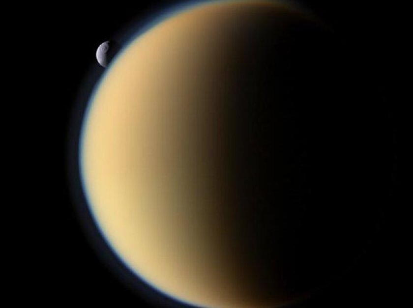 Titan overwhelms Tethys, another of Saturn's moons.