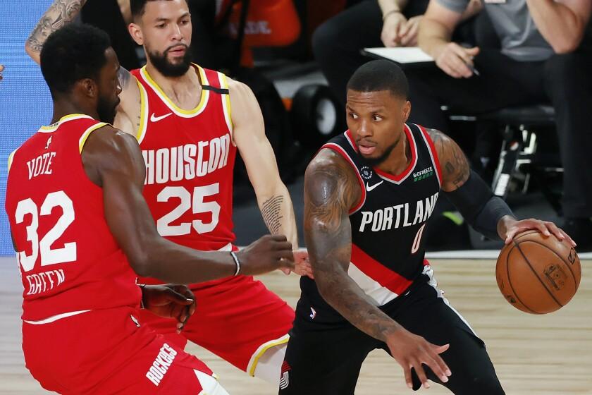 El jugador de los Trail Blazers de Portland Damian Lillard (0) conduce la pelota ante sus rivales de los Rockets de Houston Jeff Green (32) y Austin Rivers (25), en la primera mitad del juego de la NBA que enfrentó a ambos equipos, el 4 de agosto de 2020, en Lake Buena Vista, Florida. (Kevin C. Cox/Pool Foto via AP)