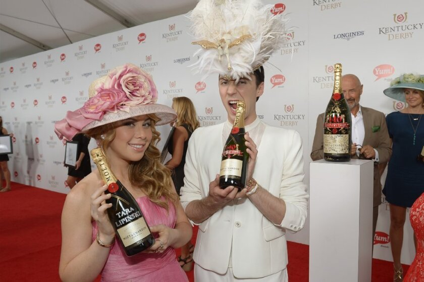 Johnny Weir wears a flying Pegasus hat as he and his co-commentator Tara Lipinski display bottles of Champagne at the Kentucky Derby.