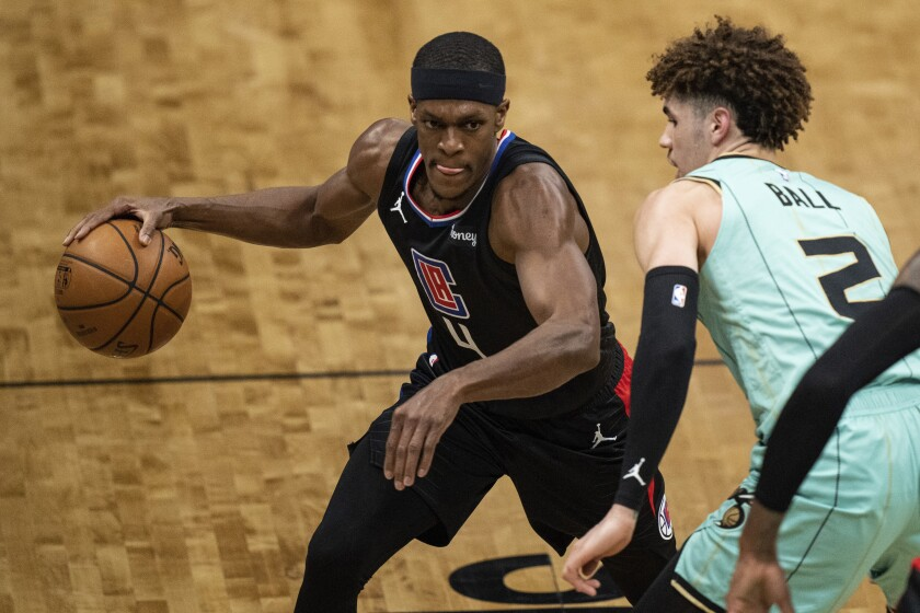 Clippers guard Rajon Rondo brings the ball up court while guarded by Charlotte's LaMelo Ball.