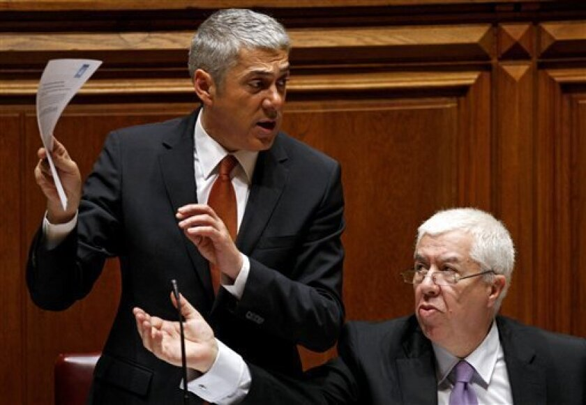FILE-- In this Nov. 2, 2010, file photo, Portuguese Prime Minister Jose Socrates, left, and Portuguese Finance Minister Fernando Teixeira dos Santos gesture during the 2011 state budget debate at the Portuguese parliament in Lisbon. Europe's debt crisis looked increasingly likely to claim another victim on Monday Jan. 10, 2011, as Portugal's borrowing rates spiked to euro-era highs amid reports Germany and France are pushing it to accept outside help and prevent contagion to other countries. (AP Photo/ Francisco Seco, File)