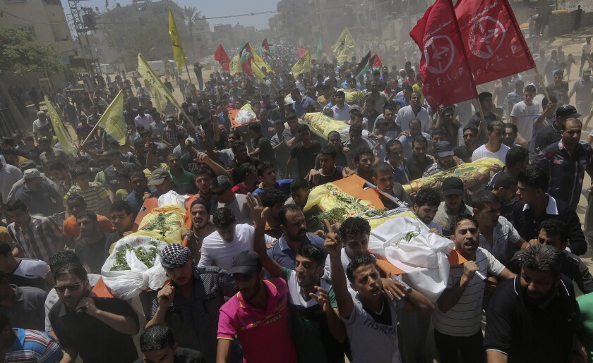Palestinians carry the bodies of seven people killed in an Israeli strike at the Khan Yunis refugee camp in the southern Gaza Strip on July 9.