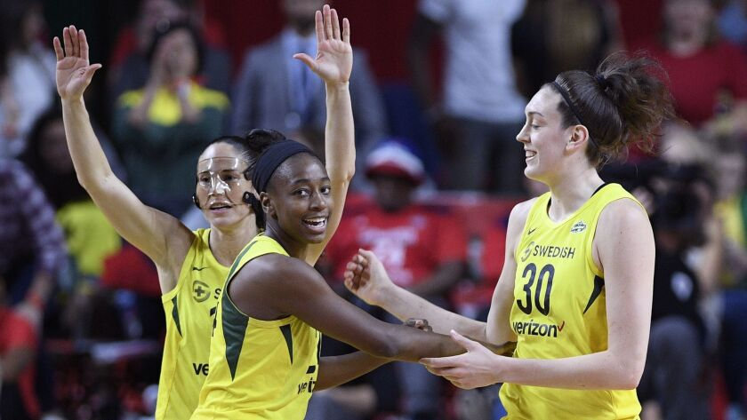 Seattle Storm guard Sue Bird, back left, Jewell Loyd, center, and Breanna Stewart (30) react during