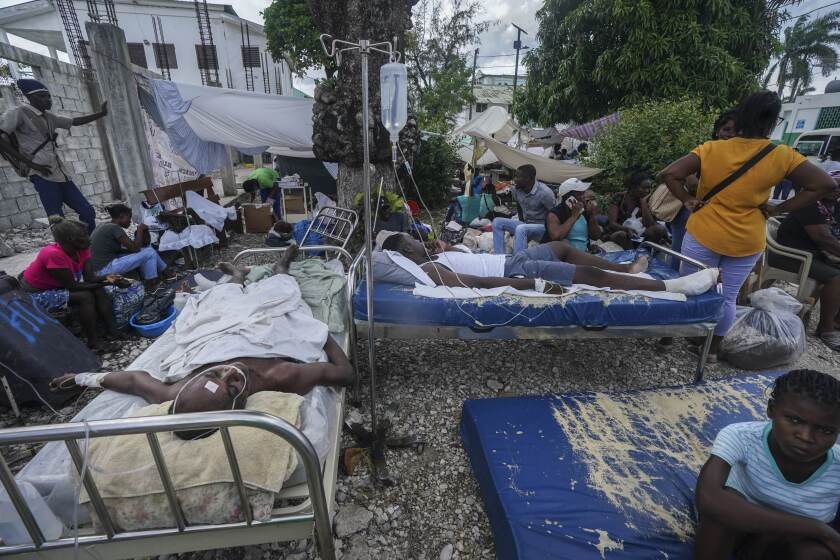 Injured people lying in beds outside a hospital
