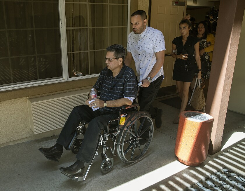 Russell French, left, and son Kevin leave a news conference in Corona.