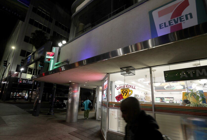 Homeless men mill around outside a 7-Eleven store in Long Beach.