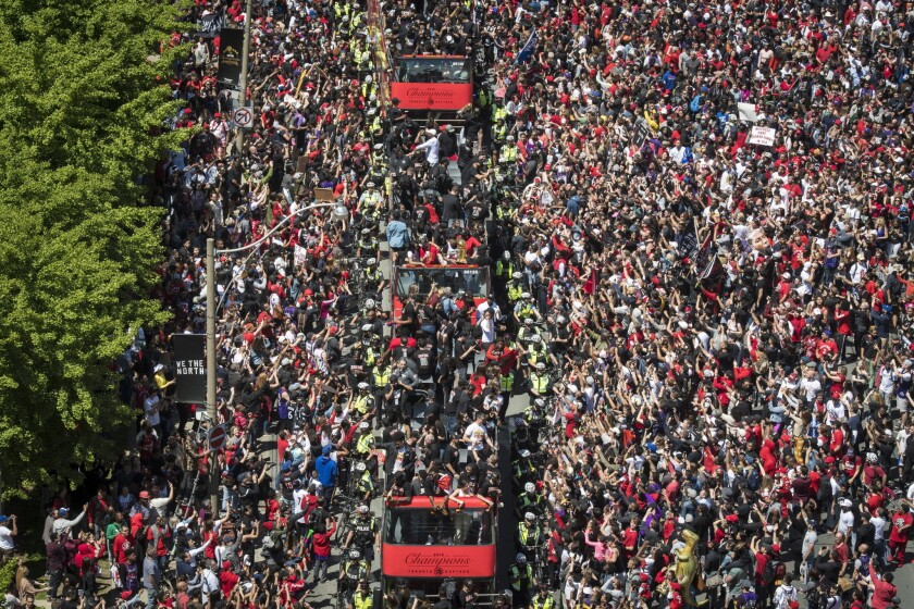 Members of the Toronto Raptors NBA basketball championship team ride on buses during a victory parad