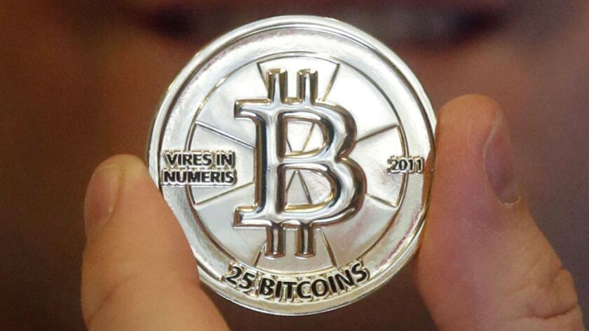 A man holds a token bearing the symbol of digital cryptocurrency bitcoin.