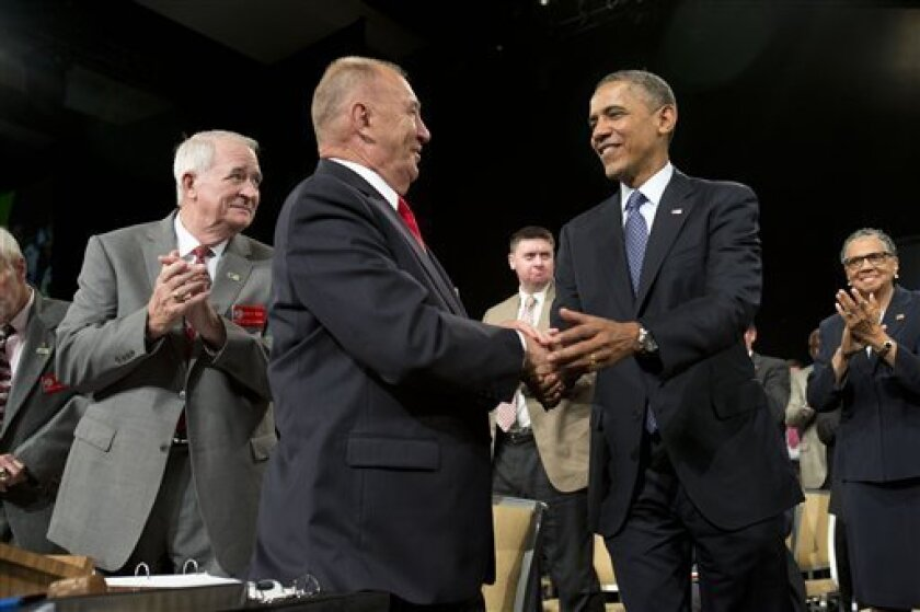 President Barack Obama shakes hands with Disabled American Veterans National Commander Larry Polzin, before speaking in Orlando, Fla., Saturday, Aug. 10, 2013. After the event the Obamas will travel to Martha's Vineyard, Mass. to begin their family vacation. (AP Photo/Jacquelyn Martin)