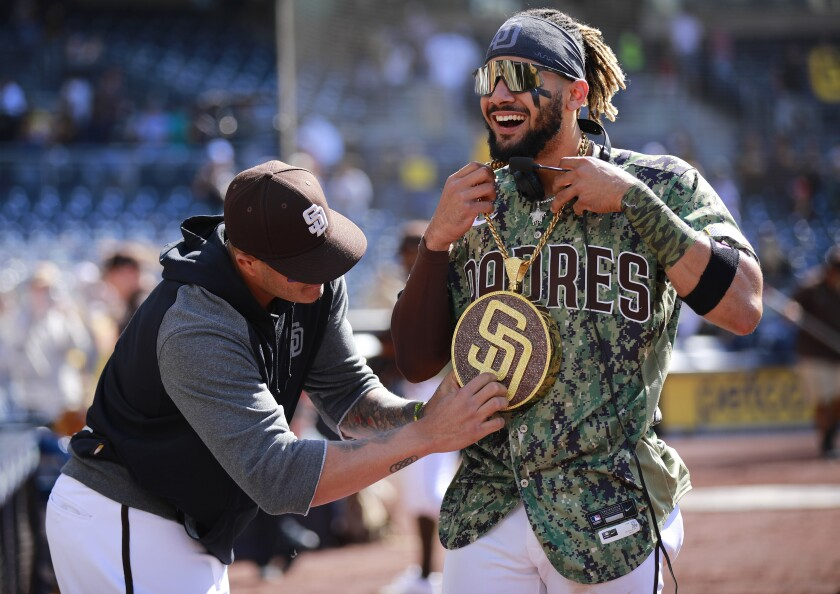 Manny Machado puts the Padres' new 'Swagg Chain' on Fernando Tatis Jr. after Sunday's 9-2 win against the Seattle Mariners