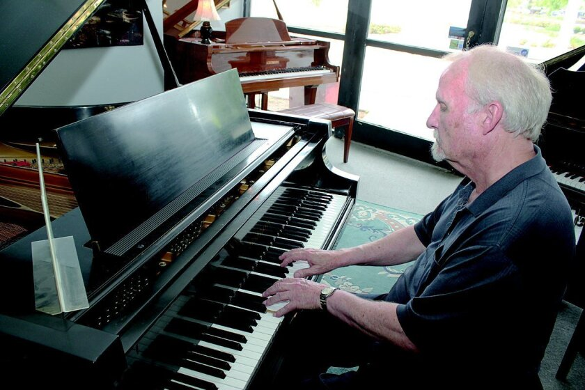 In this 2013 photo, Peter Schroeder plays a piano he told La Jolla Light was used in concert by Leonard Bernstein. Later that year, Schroeder contacted the Light to say he was looking to sell his business to someone who would keep it in Bird Rock.