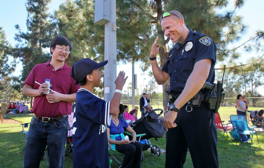 San Diego Police Officer Jeff Williams greets Special Olympics athlete Jason Tang at the San Diego County Regional Fall Games of the Special Olympics at Rancho Bernardo Recreation Park. At far left is Jason's dad, Steven Tang.