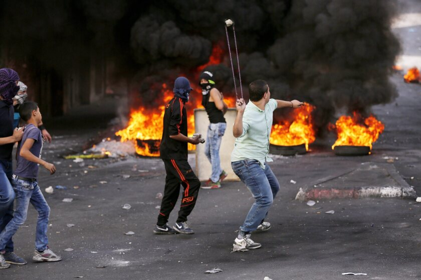 Palestinian protesters sling stones at Israeli soldiers during clashes in the West Bank city of Hebron on Oct. 22, 2015.