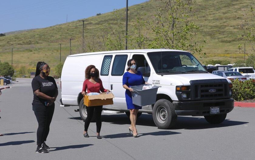 Lorena Gonzalez Fletcher (r) and Claudia Watson (m) attempted to deliver boxes containing approximately 1,000 face masks. The masks are for use by ICE detainees and U.S. Marshall inmates at the Otay Mesa Detention Center run by CoreCivic in San Diego. Attempts to deliver the masks were stopped by guards at the facility.