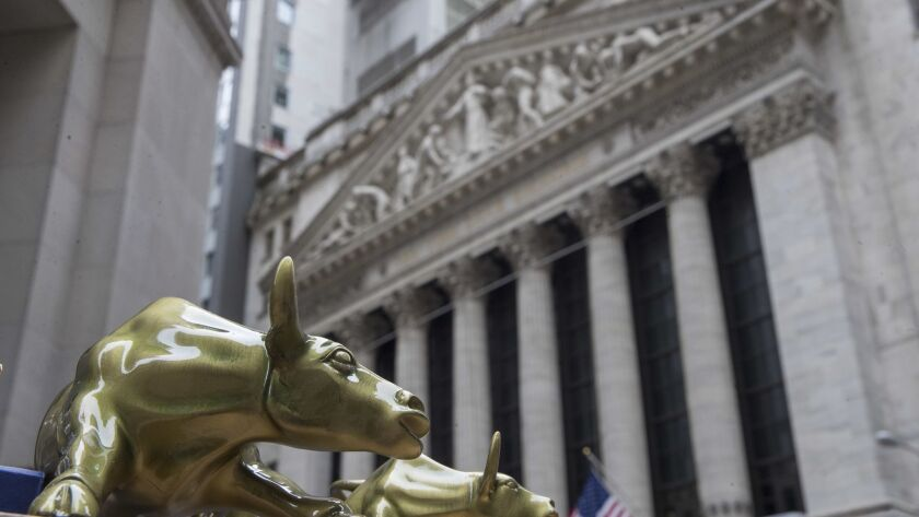 """Small replicas of Arturo Di Modica's """"Charging Bull"""" statue are displayed on a street vendor's table outside the New York Stock Exchange."""