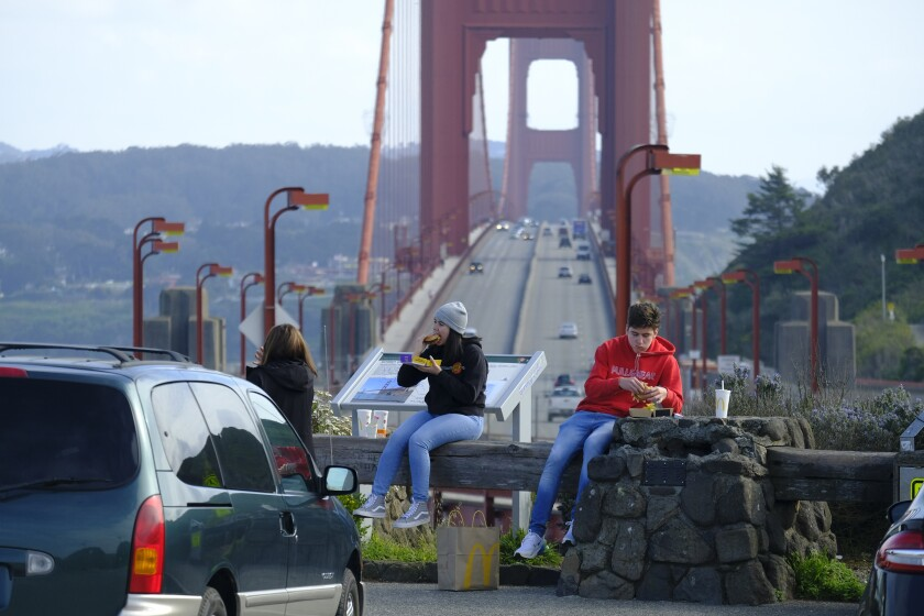People eat McDonald's while sitting at a vista point by the Golden Gate Bridge.